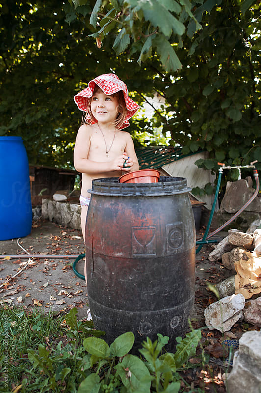 Little girl in red panama hat near the water barrels by Sveta SH for Stocksy United