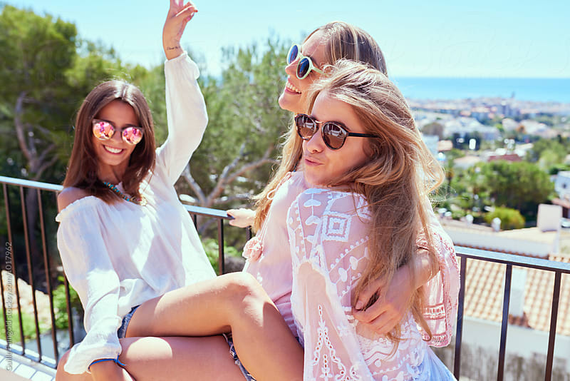 Three friends having fun on balcony against of cityscape by Guille Faingold for Stocksy United