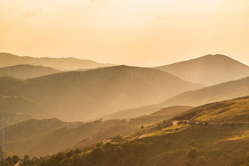 sunbeams advancing through the mountains at dusk by Javier Pardina for Stocksy United