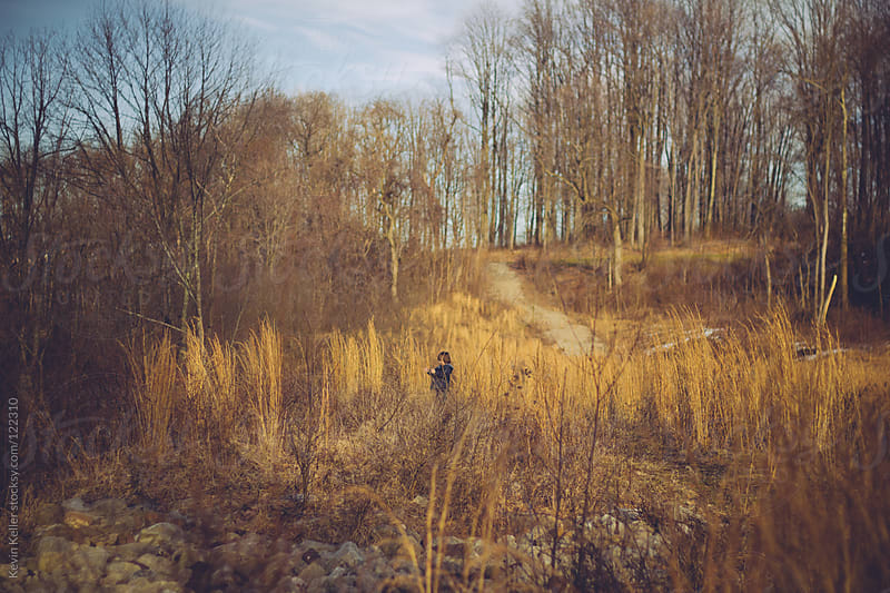 Young Boy Exploring in the Woods in March by Kevin Keller for Stocksy United