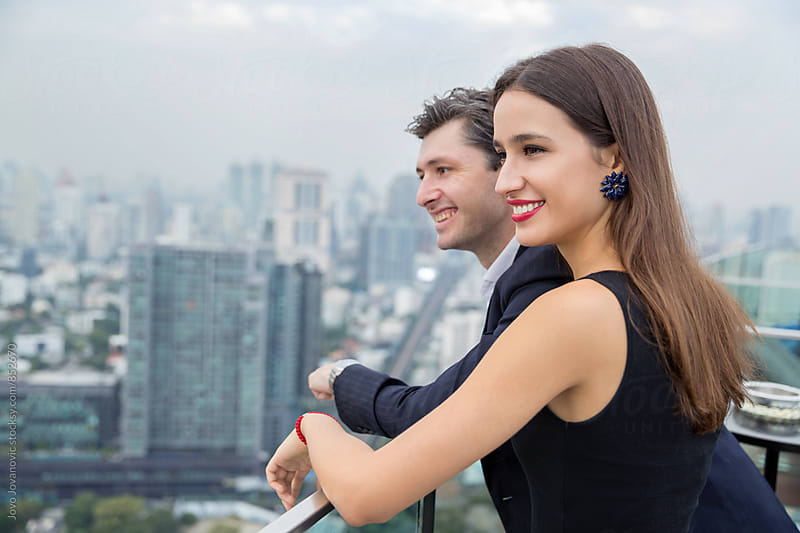 Handsome young couple smiling as they enjoy the view of a city skyline in a modern rooftop bar  by Jovo Jovanovic for Stocksy United