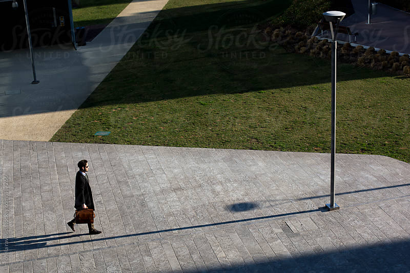 Businessman walking outdoors with his briefcase by michela ravasio for Stocksy United