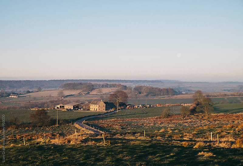 Moon over a farm at sunrise. Derbyshire, UK. by Liam Grant for Stocksy United