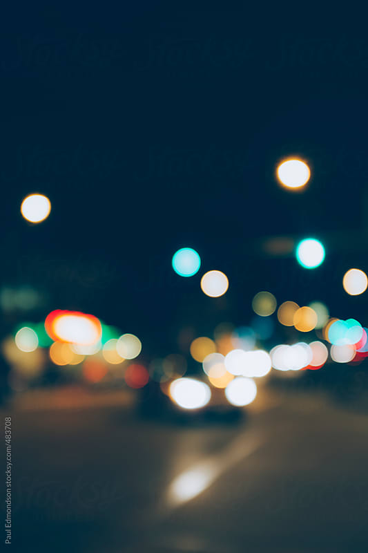Car headlights and traffic lights at night, blurred focus by Paul Edmondson for Stocksy United