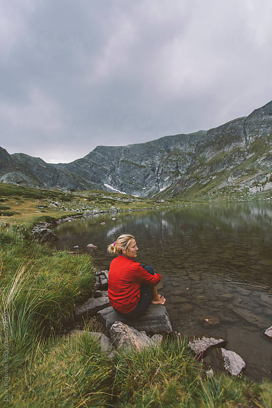 A woman sitting on a mountain lake by Dejan Ristovski for Stocksy United