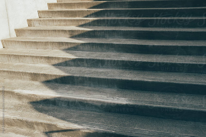 Concrete steps outside modern building, casting shadows by Paul Edmondson for Stocksy United