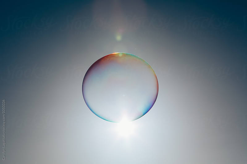 Single large soap bubble against blue sky by Carolyn Lagattuta for Stocksy United
