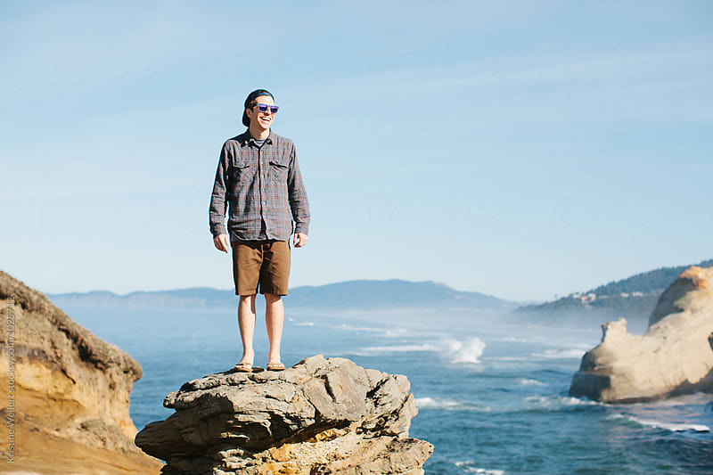 Man standing on a rock with the ocean in the background by Kristine Weilert for Stocksy United