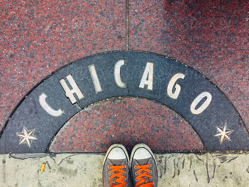 Shoes in front of a Chicago sign on a sidewalk by Gabriel (Gabi) Bucataru for Stocksy United