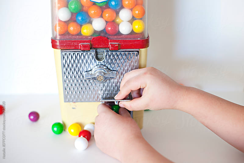 a child's hands reach to get gum balls out of machine by Natalie JEFFCOTT for Stocksy United