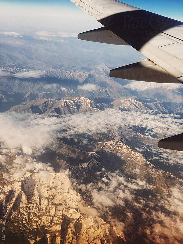 View from an aeroplane window at sunrise by Maja Topcagic for Stocksy United