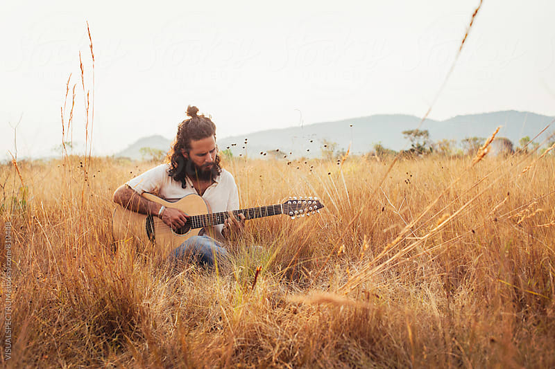 Bearded Young Male Musician Playing Guitar in Dry Grassland by VISUALSPECTRUM for Stocksy United