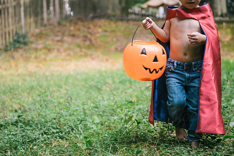 toddler in super hero cape costume is ready to go trick or treating for Halloween by Tara Romasanta for Stocksy United