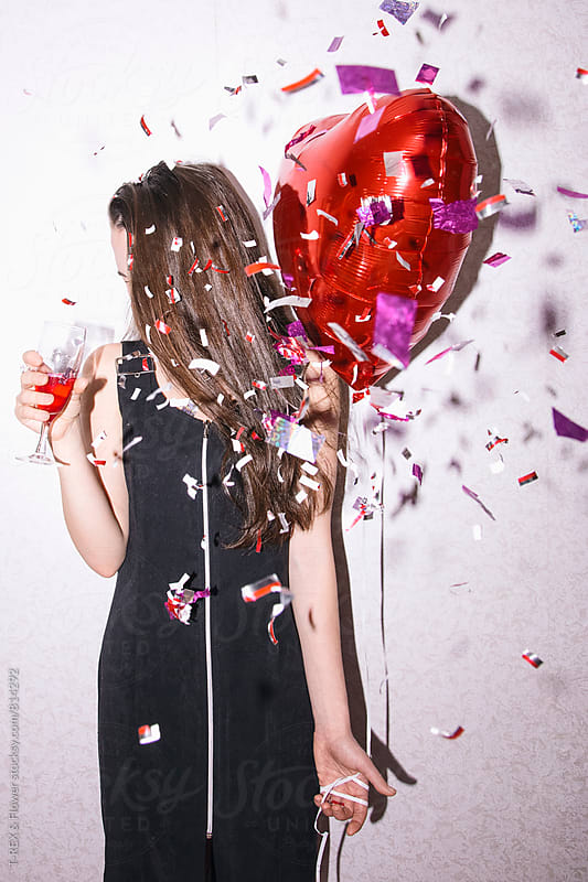 Young woman in black dress holding red balloon and glass of champagne by Danil Nevsky for Stocksy United