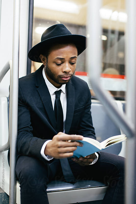 Businessman sitting on subway reading a book. by BONNINSTUDIO for Stocksy United
