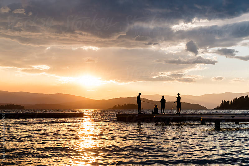 People fishing on pier of lake Pend Oreille by Trent Lanz for Stocksy United