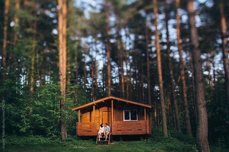 Young couple sitting on the porch of their house in the forest by Evgenij Yulkin for Stocksy United