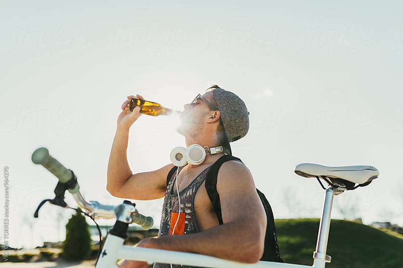 Young Man Drinking a Beer at Sunset by Victor Torres for Stocksy United