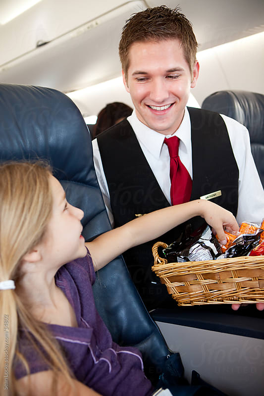 Airplane: Attendent Offering Snacks to Child by Sean Locke for Stocksy United