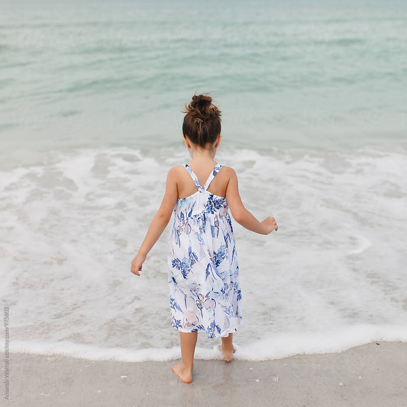Young girl dipping toes into the ocean by Amanda Worrall for Stocksy United