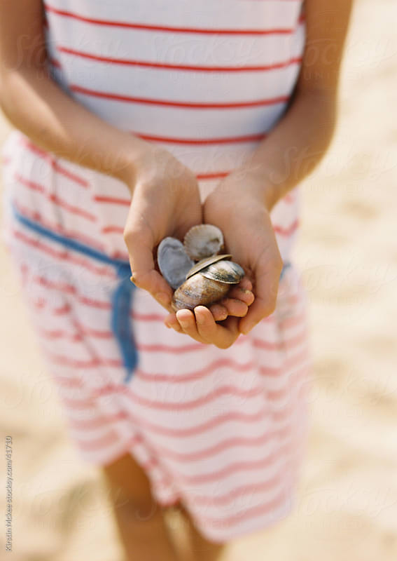 A girl in a striped dress holds shells on a sandy beach in England by Kirstin Mckee for Stocksy United