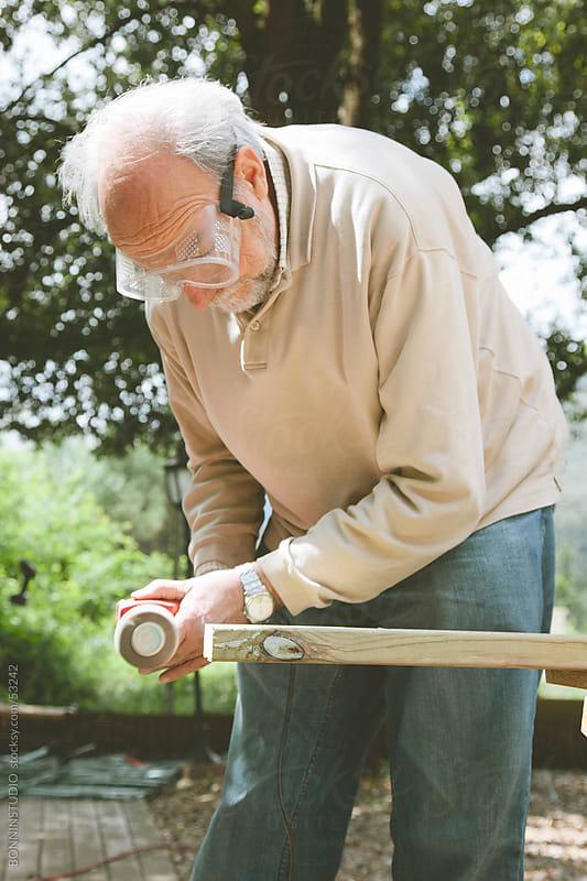 Old man sanding wood in his garden. DIY by BONNINSTUDIO for Stocksy United
