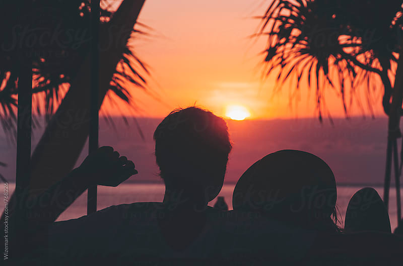 Anonymous, unrecognizable silhouetted couple watching beautiful sunset by Wizemark for Stocksy United
