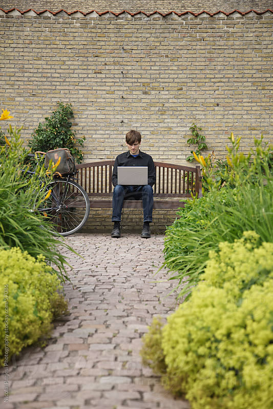 Man with laptop in a park by Nicolai Perjesi Photography for Stocksy United