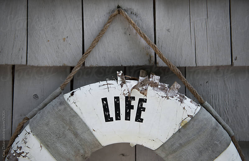 Old life preserver hangs on a shingled exterior wall by Cara Dolan for Stocksy United