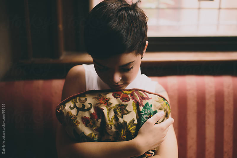 Beautiful girl hugging a pillow on vintage couch by Gabrielle Lutze for Stocksy United