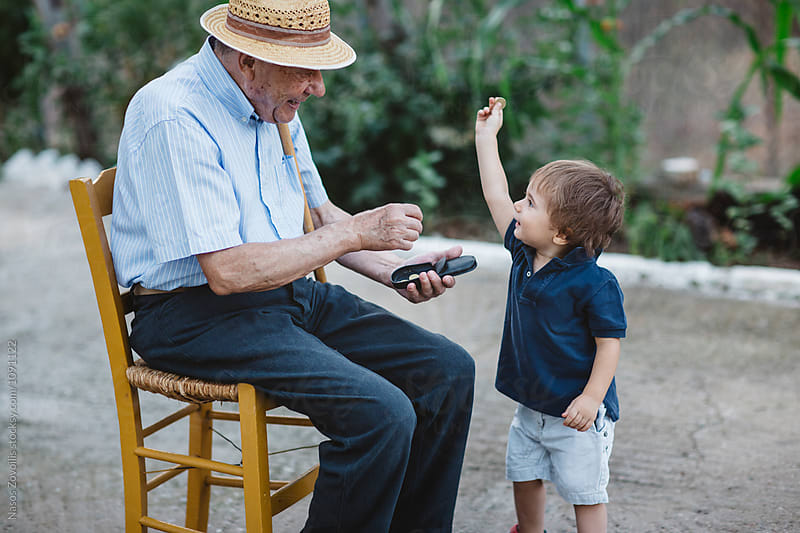 Grandfather giving money to his grandchild by Nasos Zovoilis for Stocksy United