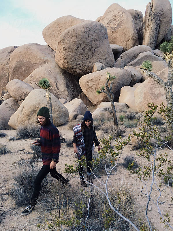 Man and Woman Walking Around Boulders by Kevin Russ for Stocksy United
