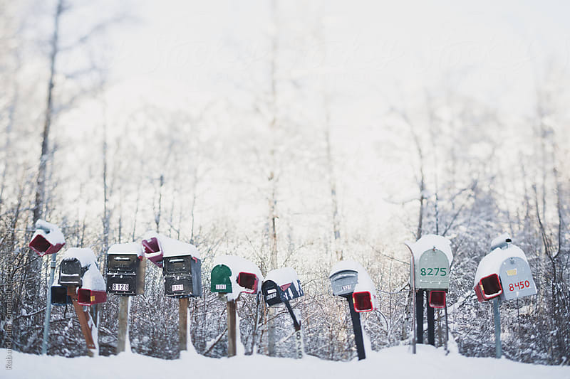 A line of mailboxes with fresh snow on them by Rob and Julia Campbell for Stocksy United