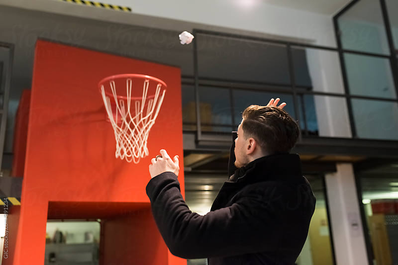 Man throwing a paper ball in the basket by Simone Becchetti for Stocksy United