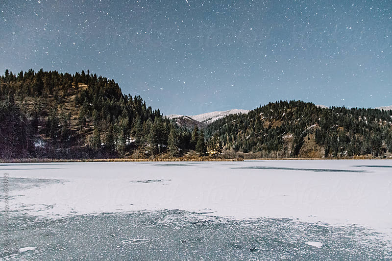 Sky with stars above frozen lake and mountains in Idaho by Justin Mullet for Stocksy United