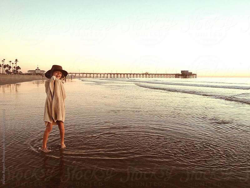 happy little girl wearing hat standing on beach in towel by Kristin Rogers Photography for Stocksy United