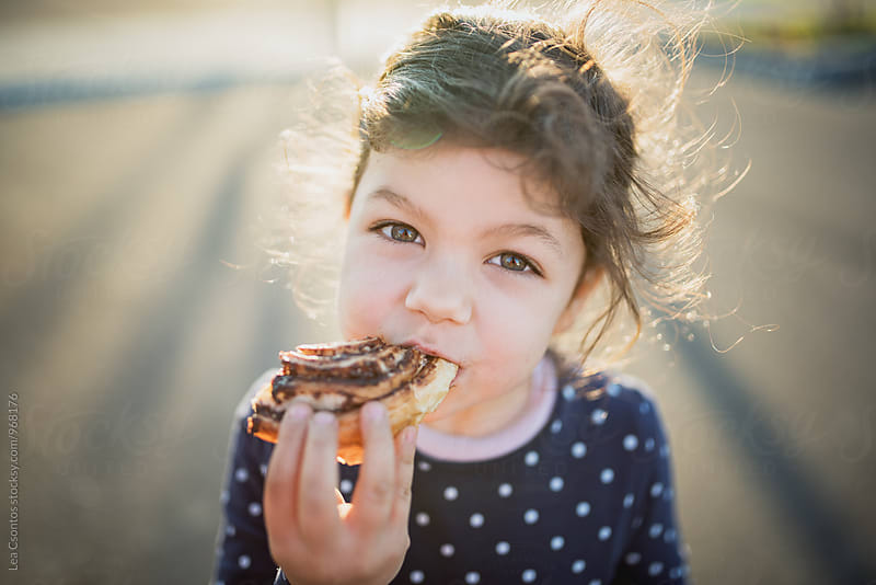 Portrait of a girl eating chocolate rolls by Lea Csontos for Stocksy United