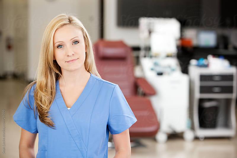Blood Bank: Cheerfule Nurse with Equipment Behind by Sean Locke for Stocksy United