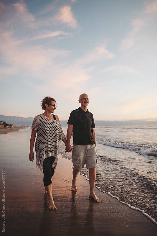 Content middle aged, retired couple walk together outside on ocean beach by Rob and Julia Campbell for Stocksy United