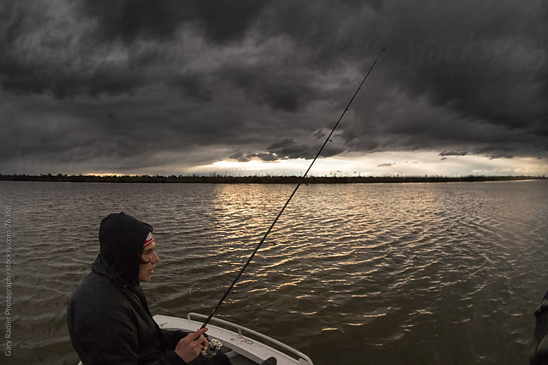 Young Adult Fisherman and an Approaching Storm by Gary Radler Photography for Stocksy United