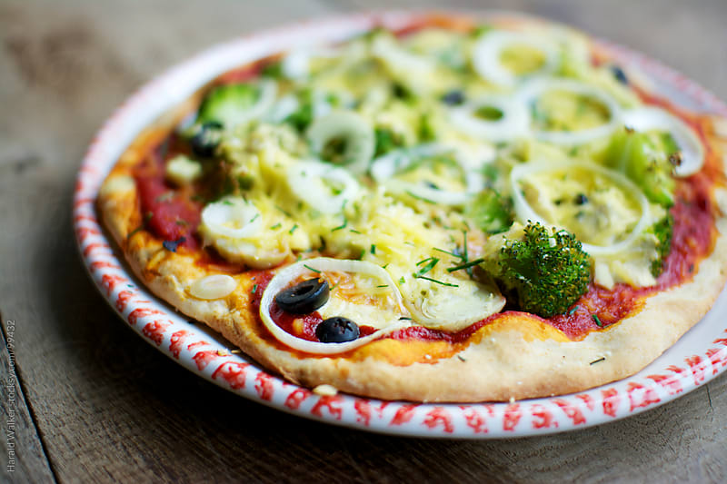 Artichoke broccoli pizza by Harald Walker for Stocksy United