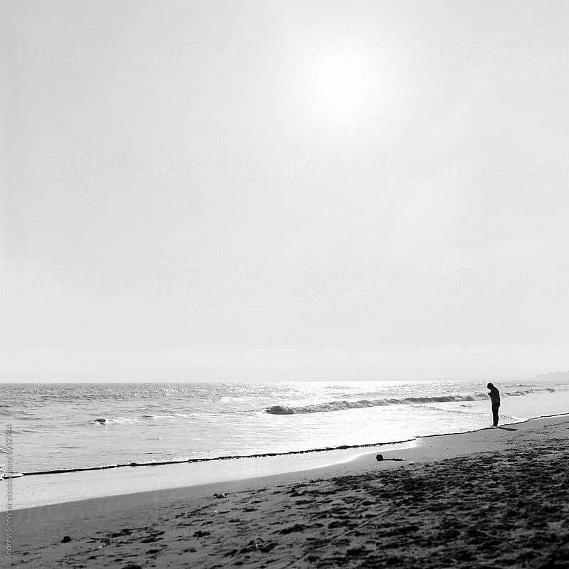 Woman standing with her phone by the sea by Andrew Spencer for Stocksy United