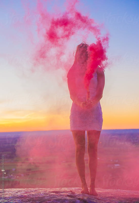 Woman with Smoke Bomb At Sunset by Brian McEntire for Stocksy United