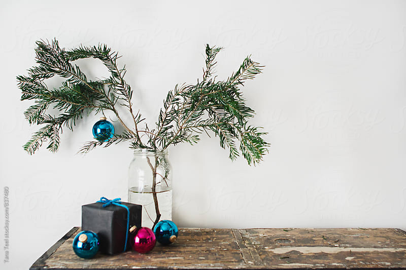 evergreen branch in glass jar with ornaments and gift by Tana Teel for Stocksy United