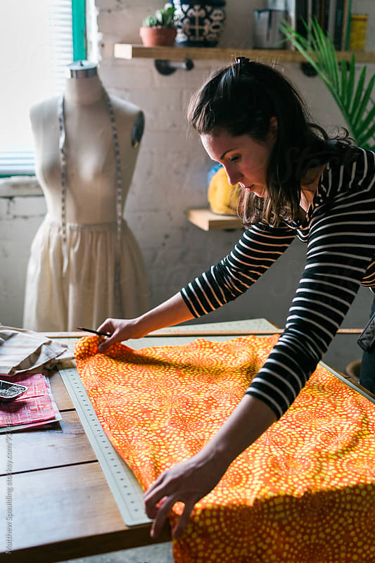 Designer measuring orange fabric for clothing pattern by Matthew Spaulding for Stocksy United