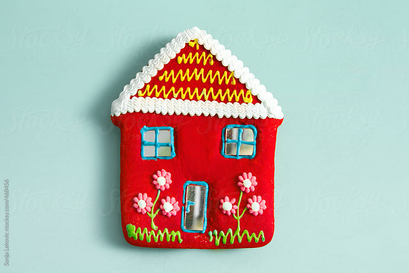 red candy house on baby blue background with copyspace by Sonja Lekovic for Stocksy United