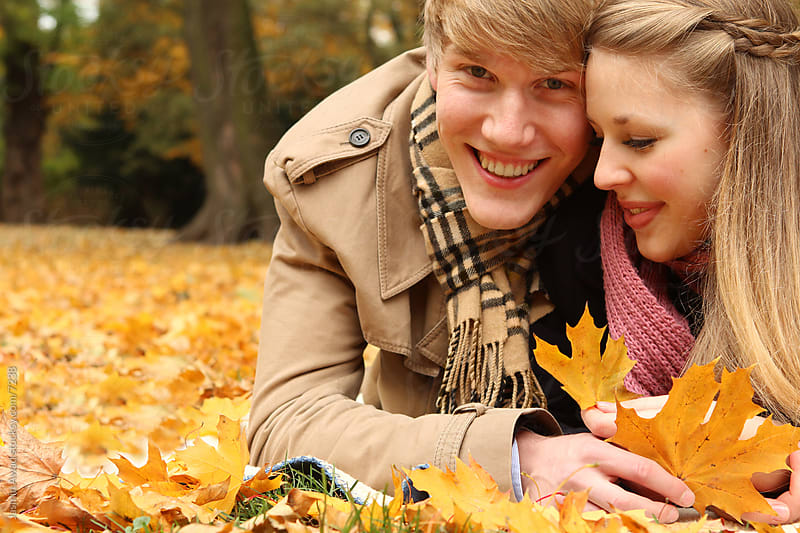 Young couple with autumn leaves by Jasmin Awad for Stocksy United