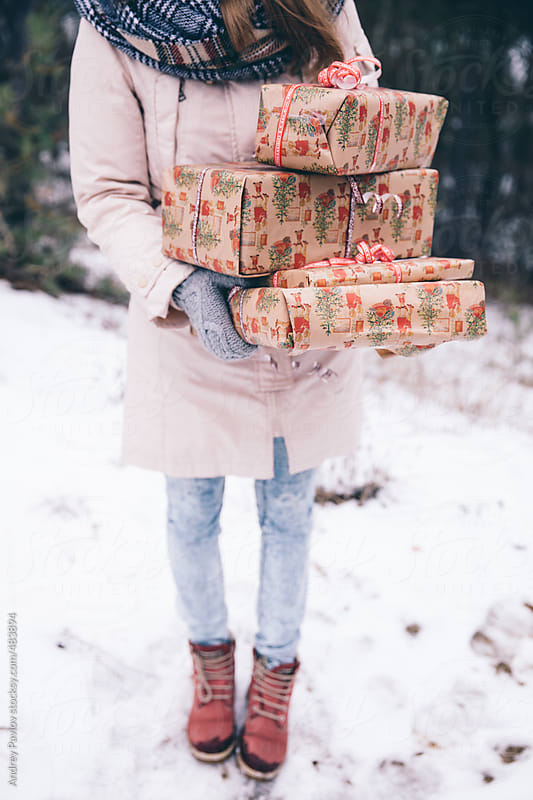 Woman carries an armload of gifts by Andrey Pavlov for Stocksy United
