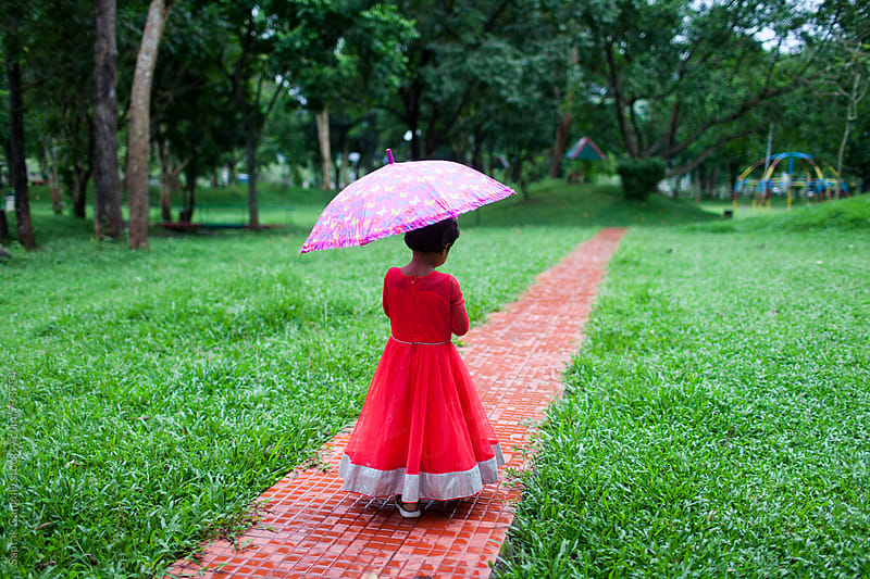 Little girl with umbrella walking along a path in the park by Saptak Ganguly for Stocksy United