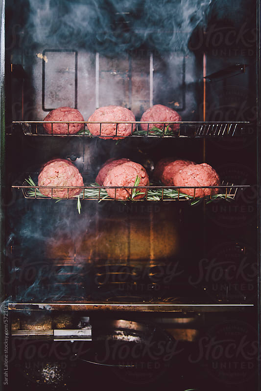 Gourmet meatballs inside a smoker, cooking. by Sarah Lalone for Stocksy United